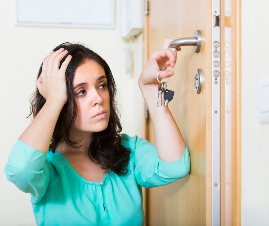 woman looking at broken lock of outer door